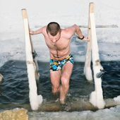 The man gets out of the ice on the Lake in winter — Stock Photo
