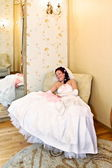 The bride in her wedding dress is sitting in his chair and smiles — Stock Photo