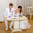 Bride and groom signs the book — Stock Photo