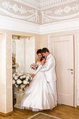 The groom embracing bride near the mirror — Stock Photo