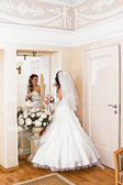 Bride in wedding dress looks in the mirror — Stock Photo