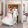 Bride and groom emerge from doors of Palace of weddings — Stock Photo #32423503