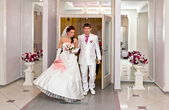 Bride and groom emerge from the doors of the Palace of weddings — Stock Photo