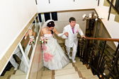 The bride and groom's wedding attire go up the stairs — Stock Photo