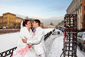 Newlyweds in wedding attire cuddling the winter backdrop of St. Petersburg — Stock Photo