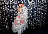 Newlyweds in wedding attire posing in scenery of glass balls — Stock Photo