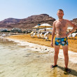 A man in swimming trunks stands on the shore of the dead sea in Israel against the background of the mountains A man in swimming trunks stands on the shore of the dead sea in Israel against the backg — Stock Photo #32698901