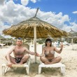 Tanned girl in bikini and a man sitting under an umbrella on the — Stock Photo