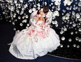 Newlyweds in wedding attire posing in scenery of glass balls — Stock Photo