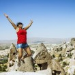 Stock Photo: Happy girl jumping on background of cave city in Cappado