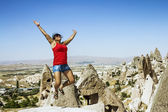 Happy girl jumping on the background of the cave city in Cappado — Stock Photo