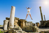 Girl in jump amid the ruins of Carthage in Tunisia — Stock Photo