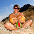 Tanned girl with melons and watermelons posing against a backdrop of mountain scenery — Stock Photo