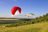 Multiple paragliders soar in the air amid wondrous landscape — Stock Photo