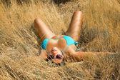 Tanned girl in bikini lying in high dry grass — Stock Photo