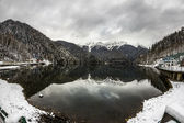 Alpine Lake Ritsa in winter under gloomy clouds, Abkhazia — Stock Photo