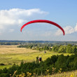 Stock Photo: Paraglider soar in air amid wondrous landscape