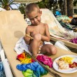 The little boy is sitting on a lounge chair with a plate of food — Stock Photo