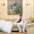 Stock Photo: Bride and groom in wedding attire have settled down on couch bride and groom in wedding attire have settled down on couch