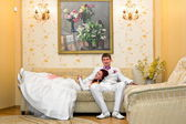 The bride and groom in wedding attire have settled down on the couch The bride and groom in wedding attire have settled down on the couch — Stock Photo