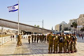 A squad of Israeli soldiers on the square near the Western Wall under national flag (Jerusalem) — Stock Photo