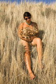 Tanned nude girl lies in a high dry grass — Stock Photo