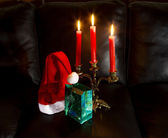 Hat of Santa Claus with gift and chandelier with candles — Photo