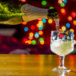 Sparkling wine is poured into the glass against the backdrop of — Stock Photo