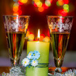 Goblets with sparkling wine and a burning candle on the backgrou — Stock Photo