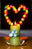 Burning candle amid colorful heart-shaped Bokeh — Stock Photo
