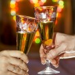 Stock Photo: Hands with glasses of sparkling wine against the backdrop of a c