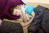 The little boy is sleeping in the bed with a small dog — Stock Photo