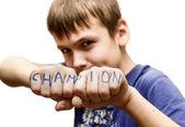 Un garçon se tient dans une pose de combat, avec le mots « champion » sur — Photo