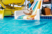 A man rolls down a hill in a aquapark on a bright sunny day — Stock Photo
