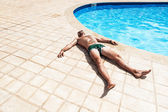 The man sunning by the pool — Stock Photo
