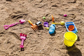Colorful children's toys scattered on the sand at the beach — Stock Photo