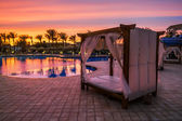 Beach bed with canopy by the pool on the beach — Stok fotoğraf