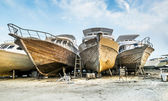Old boats are being repaired on the shore at the port  — Stock Photo