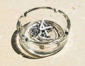 Cigarette butts from ash in the glass ashtray — Stock Photo