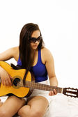 Girl strumming guitar — Stock Photo