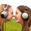 Two happy girls listening music in summer park — Stock Photo