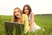 Two beautiful happy girls using a laptop in grass area — Stock Photo