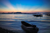 Fisherman boat under the sun set and the ray from the skyline in summer at chinese fishing village in hong kong, night scenes from hong kong to shenzhen coast — Stock Photo