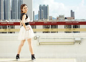 Happy pretty young city girl stand akimbo, stand up in the city life, face the difficult in hong kong china — Stock Photo