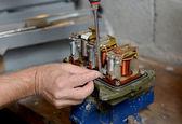 Electrician repairs a regulator of car — Stock Photo