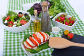 Differents salads with bottle of oil ,salt and pepper — Stock Photo