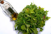 Differents green salads with bottle of oil — Stock Photo