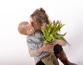 A young child offers flowers to his mom — Стоковое фото
