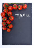 Menu on a blackboard with tomatoes — Stock Photo