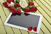 Roses and tablet — Stock Photo